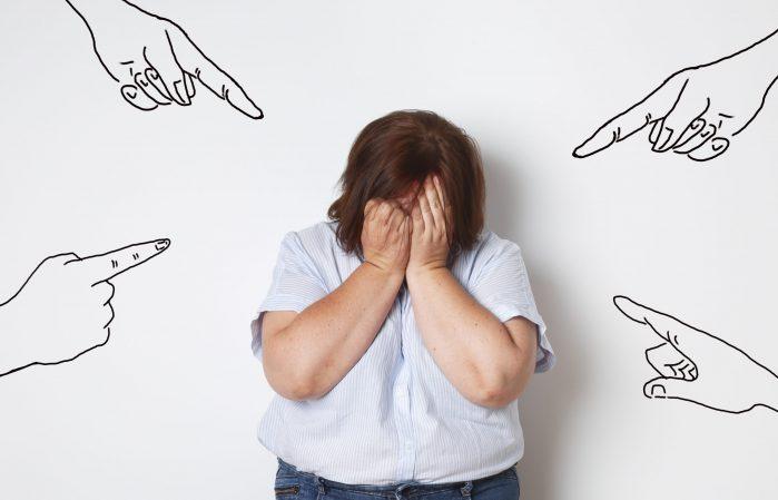 femme ronde pleurant contre un mur